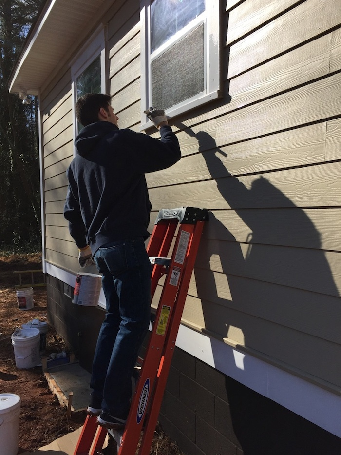 College senior David Bailey paints the exterior of the house he helped build for Lashunda McNabb, an Emory Starbucks barista. | Photo courtesy of David Bailey