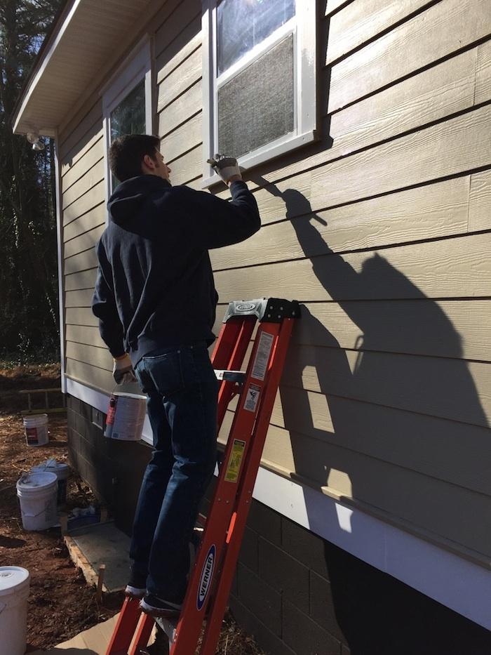 College senior David Bailey paints the exterior of the house he helped build for Lashunda McNabb, an Emory Starbucks barista. | Photo courtesy of David Bailey