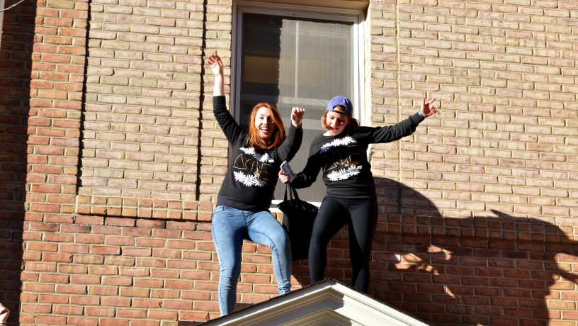 Two women dance on top of one of the sorority lodges after accepting bids to join a sorority| Photo by Erin Baker, Staff