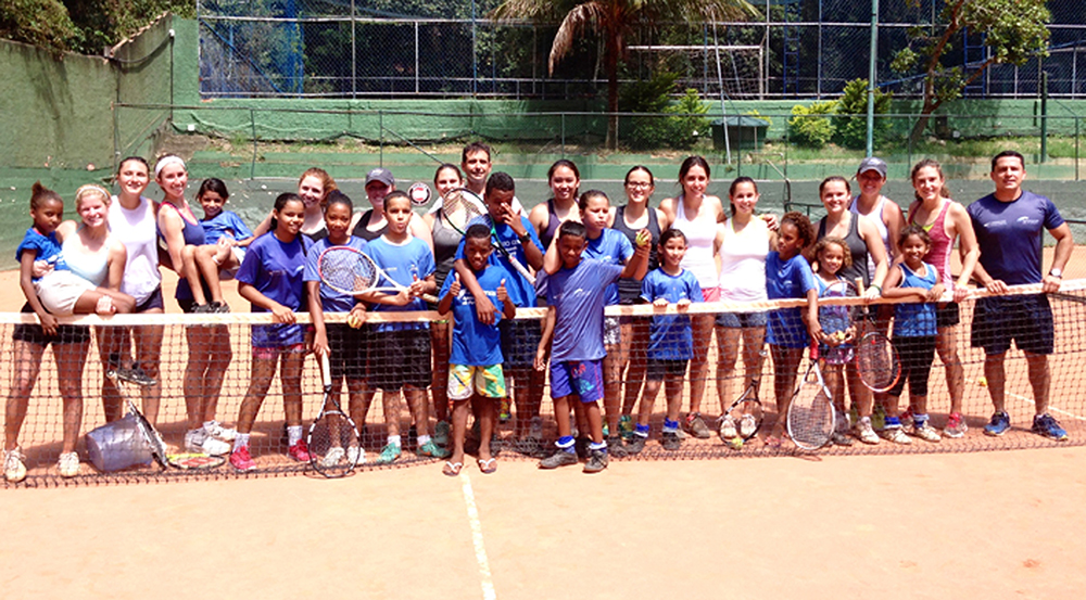 The Emory women's tennis team pauses practice for a group photo with children in Brazil. The team traveled to Rio de Janeiro over the summer to improve their own tennis skills and volunteer their time to help children learn the sport. | Courtesy of Emory Athletics.