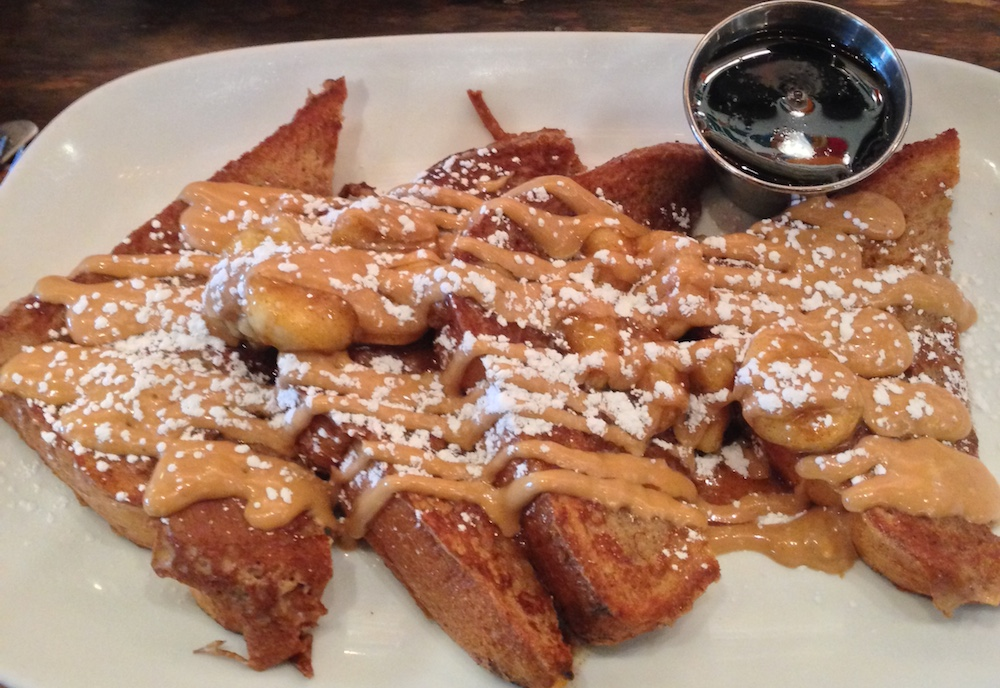Peanut butter and bananas lie gratuitously on top of fresh homemade challah French Toast at Folk Art, a southern-inspired brunch spot in Inman Park, nestled between Little Five Points and The Carter Center.