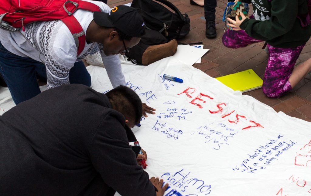 College senior Dennis Kamara (top) and College senior Harpreet Singh (bottom) sign march organizer and College freshman Ruhika Prasad's bed sheet. / Matthew Hammond, Staff