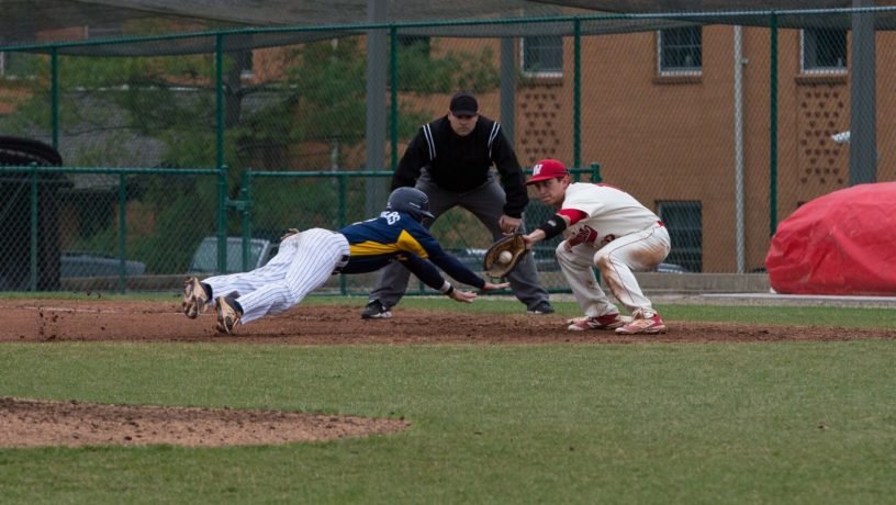 Junior infielder Nick Chambers dives to beat the tag in the Eagles' series at Washington University in St. Louis (Mo.). Photo Courtesy of Grace Burton.